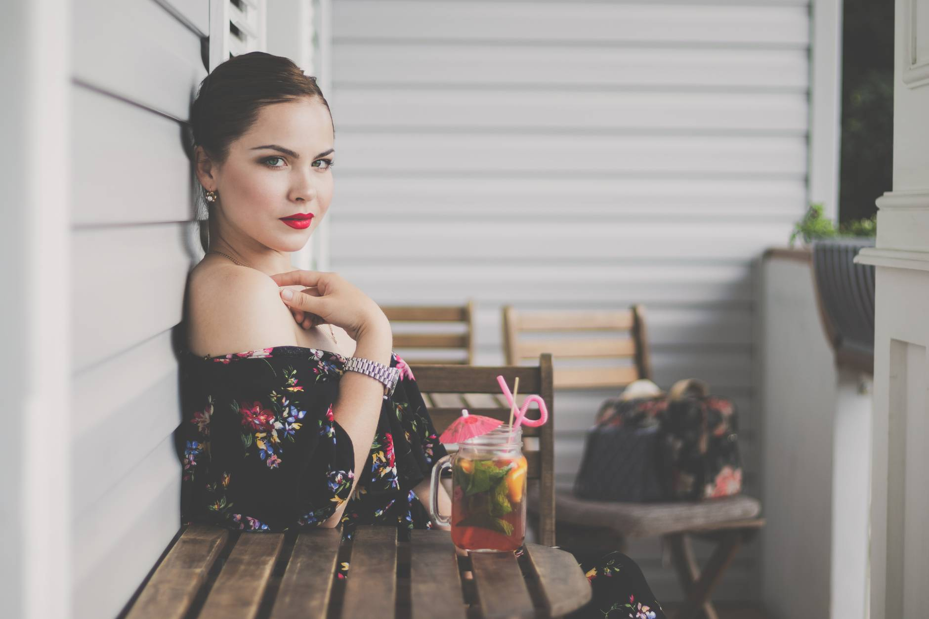 woman wearing black floral off shoulder top sitting on wooden chair